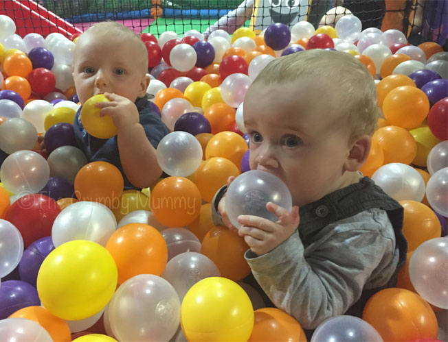 babies playing in a ball pool