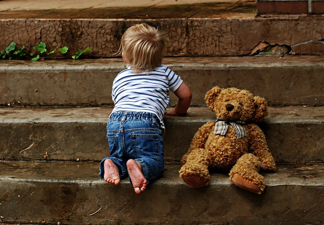 toddler on steps with teddy