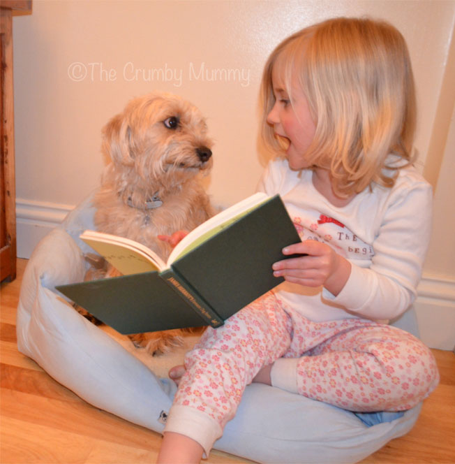 Reading her dog a bedtime story